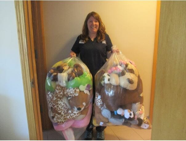 Woman holding bags filled with stuffed animals